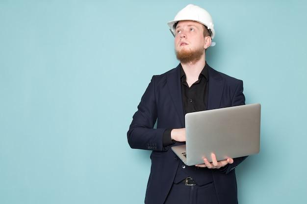 Een vooraanzicht jonge aantrekkelijke man met baard in zwart donker klassiek modern pak witte bouw helm met behulp van grijze laptop op de blauwe ruimte