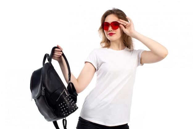 Een vooraanzicht jonge dame die in witte t-shirt rode zonnebril zwarte zak houdt glimlachend op het wit