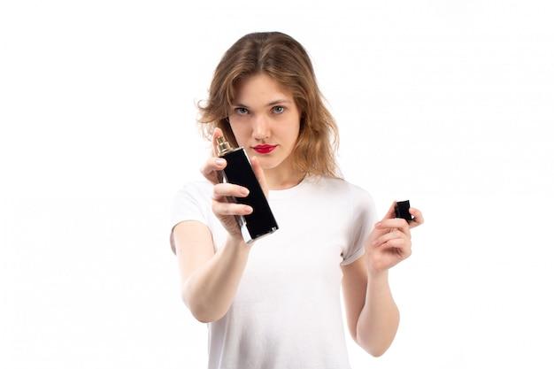 Een vooraanzicht jonge dame die in witte t-shirt zwarte parfumbuis op het wit houdt