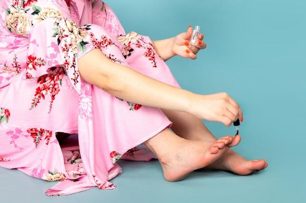 Een vooraanzicht jonge dame in bloem ontworpen roze jurk haar nagels schilderen op blauw