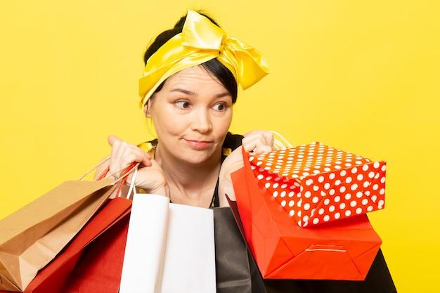Een vooraanzicht jonge dame in geel-zwart bloem ontworpen jurk met geel verband op het hoofd poseren met shopping pakketten op de gele