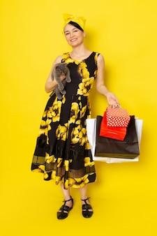Een vooraanzicht jonge dame in geel-zwart bloem ontworpen jurk met gele bandage op het hoofd met boodschappenpakketten en kitten op de gele