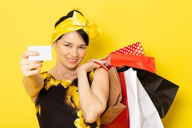 Een vooraanzicht jonge dame in geel-zwart bloem ontworpen jurk met gele bandage op het hoofd met boodschappenpakketten glimlachend op de gele