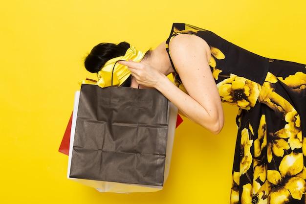 Een vooraanzicht jonge dame in geel-zwart bloem ontworpen jurk met gele bandage op het hoofd met shopping pakketten controleren ze op het geel