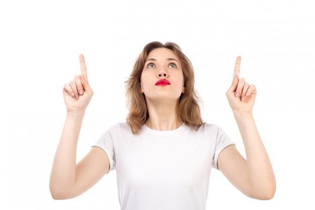 Een vooraanzicht jonge dame in het witte t-shirt stellen die de hemelen onderzoeken die op het wit denken
