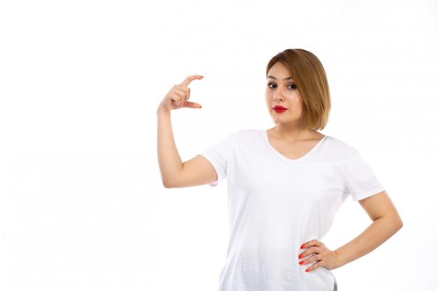 Een vooraanzicht jonge dame in het witte t-shirt stellen die grootte op het wit toont