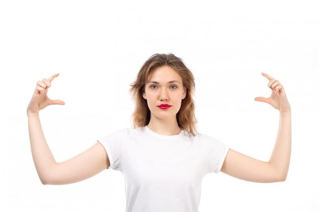 Een vooraanzicht jonge dame in het witte t-shirt stellen die grootte tonen haar vingers op het wit