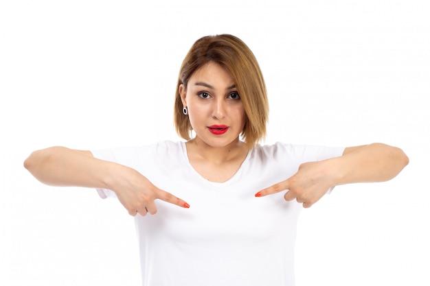 Een vooraanzicht jonge dame in het witte t-shirt stellen die haar vingers op het wit richten
