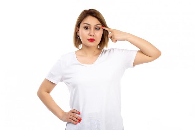 Een vooraanzicht jonge dame in het witte t-shirt stellen die op het wit denken