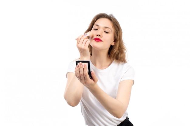 Een vooraanzicht jonge dame in wit overhemd en zwarte broek doen make-up op de witte