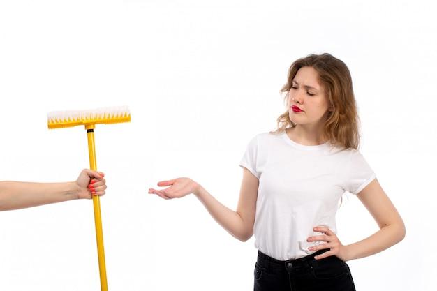 Een vooraanzicht jonge dame in wit overhemd en zwarte broek krijgen gele mop ontevreden op het wit