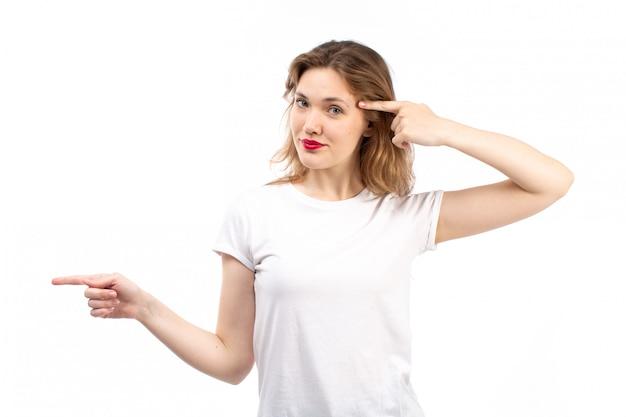 Een vooraanzicht jonge dame in wit overhemd en zwarte moderne jeans die op het wit stellen