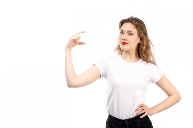 Een vooraanzicht jonge dame in wit overhemd en zwarte moderne jeans met maat op de witte