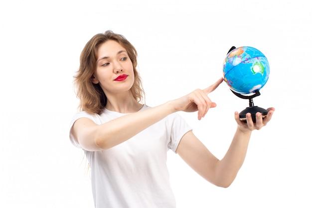 Een vooraanzicht jonge dame in wit t-shirt met kleine ronde wereldbol op de witte
