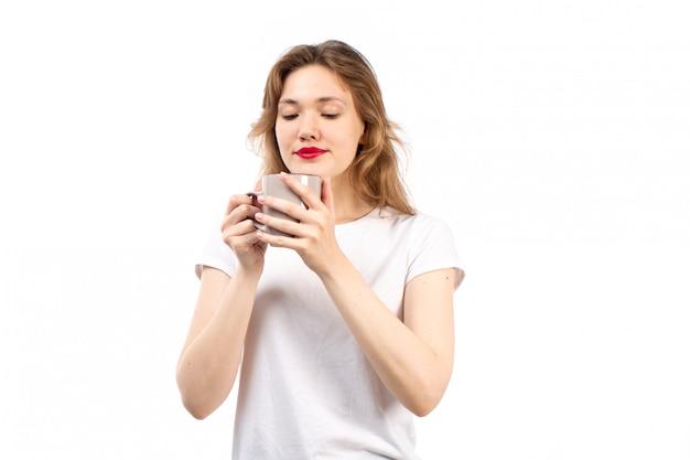 Een vooraanzicht jonge dame in witte t-shirt het glimlachen holdingskop met thee op het wit
