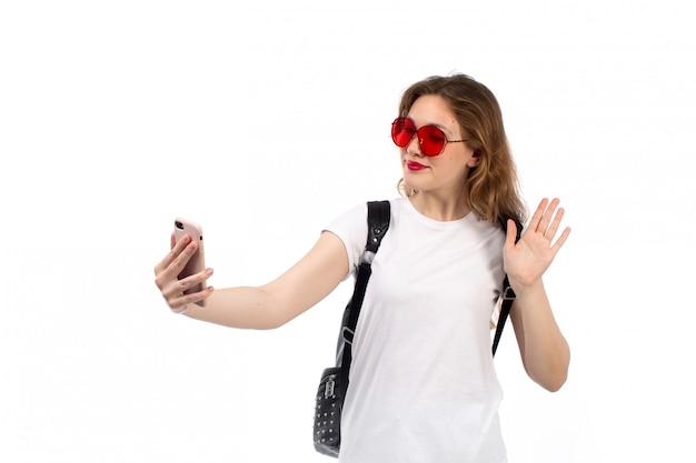 Een vooraanzicht jonge dame in witte t-shirt rode zonnebril zwarte tas glimlachend nemen selfie op het wit