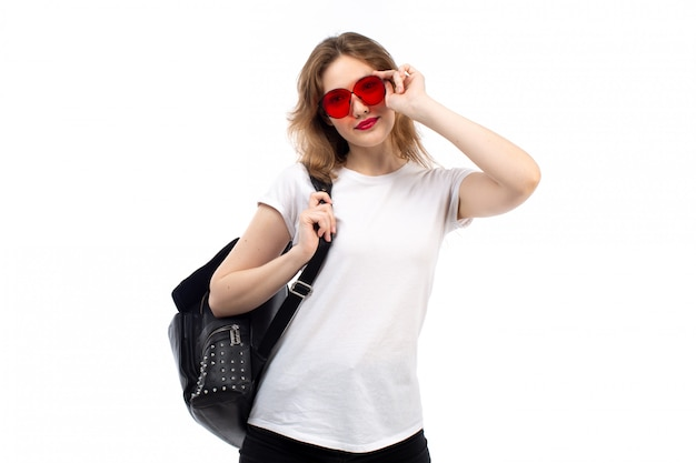 Een vooraanzicht jonge dame in witte t-shirt rode zonnebril zwarte tas lachend op de witte