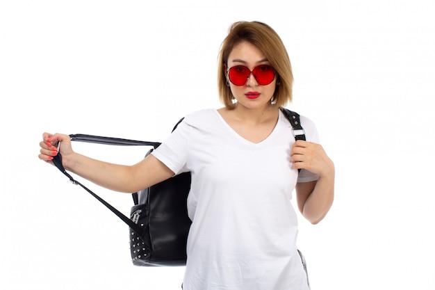 Een vooraanzicht jonge dame in witte t-shirt rode zonnebril zwarte tas op de witte