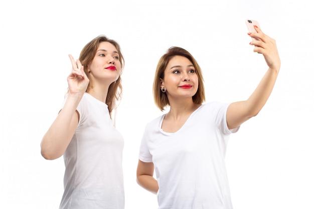 Een vooraanzicht jonge dames in witte t-shirts nemen een selfie op de witte