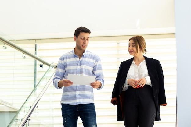 Een vooraanzicht jonge knappe man in gestreept shirt praten en bespreken van werkkwesties met jonge zakenvrouw tijdens de dag van de werkzaamheden activiteit bouwen