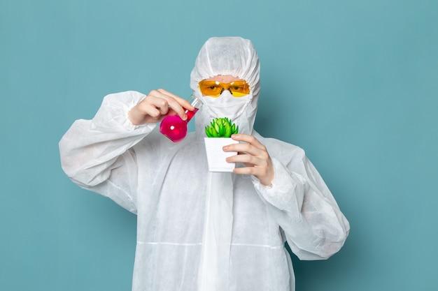 Een vooraanzicht jonge man in een wit speciaal pak met oplossing op de blauwe muur man pak gevaar speciale uitrusting kleur