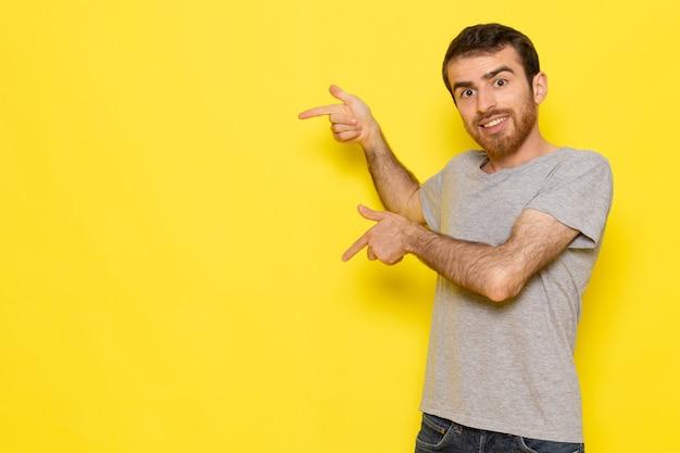 Een vooraanzicht jonge man in grijs t-shirt glimlachend en poseren op de gele muur man kleur model emotie kleding