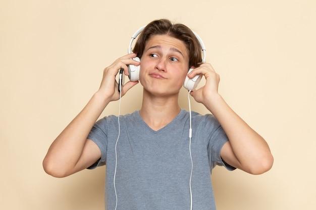 Een vooraanzicht jonge man in grijs t-shirt luisteren naar muziek