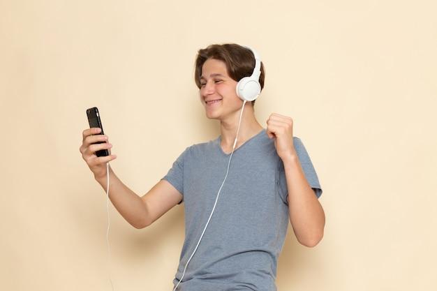 Een vooraanzicht jonge man in grijs t-shirt met behulp van telefoon luisteren naar muziek
