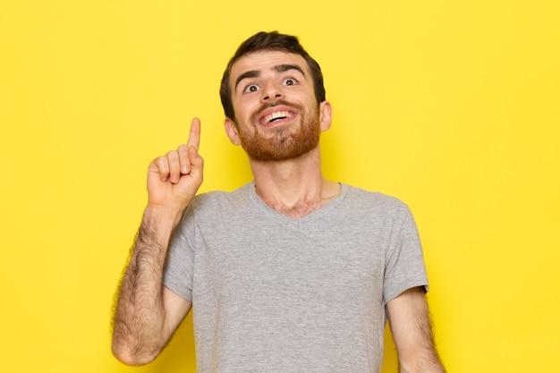 Een vooraanzicht jonge man in grijs t-shirt met grappige uitdrukking op de gele muur man uitdrukking emotie kleur model