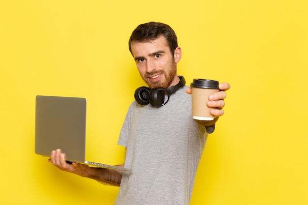 Een vooraanzicht jonge man in grijs t-shirt met koffiekopje en met behulp van laptop met glimlach op de gele muur man expressie emotie kleur model
