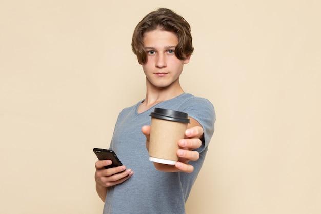 Een vooraanzicht jonge man in grijs t-shirt met koffiekopje en telefoon