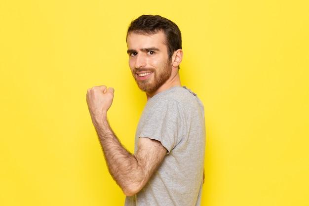 Een vooraanzicht jonge man in grijs t-shirt met opgetogen uitdrukking op de gele muur man kleur model emotie kleding