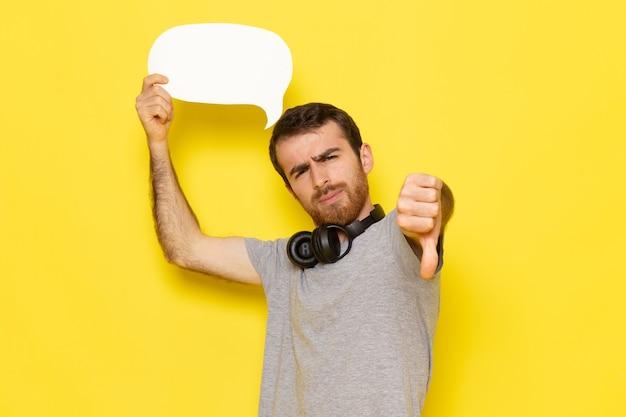 Een vooraanzicht jonge man in grijs t-shirt met wit bord op de gele muur man expressie emotie kleur model