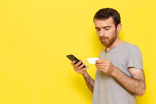 Een vooraanzicht jonge man in grijs t-shirt met zijn telefoon op de gele muur man kleur model emotie kleding