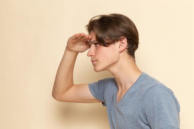 Een vooraanzicht jonge man in grijs t-shirt op zoek in de verte