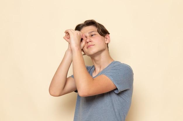 Een vooraanzicht jonge man in grijs t-shirt poseren kijkend door zijn handen