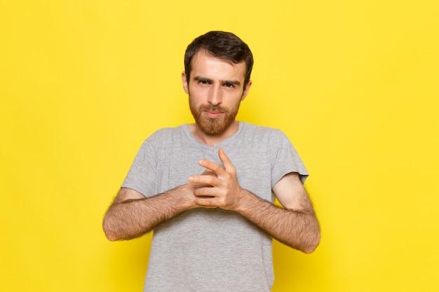 Een vooraanzicht jonge man in grijs t-shirt poseren op de gele muur man expressie emotie kleur model