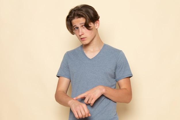Een vooraanzicht jonge man in grijs t-shirt poseren wijzend in zijn pols