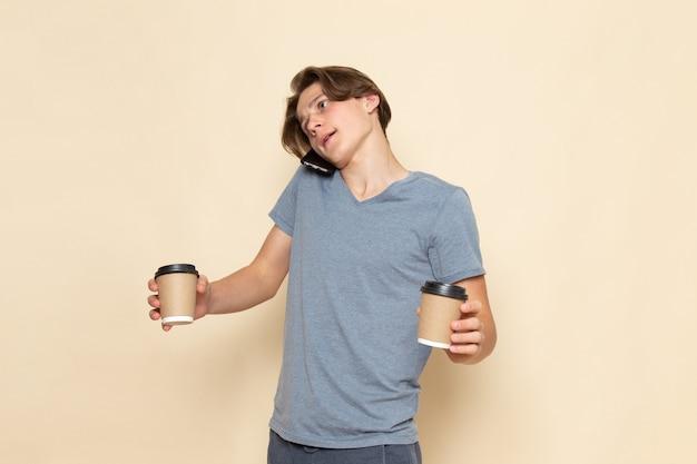 Een vooraanzicht jonge man in grijs t-shirt praten aan de telefoon met koffiekopjes