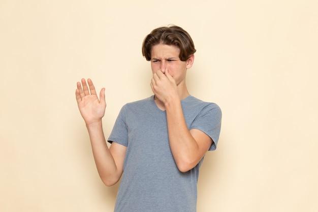 Een vooraanzicht jonge man in grijs t-shirt voor zijn neus