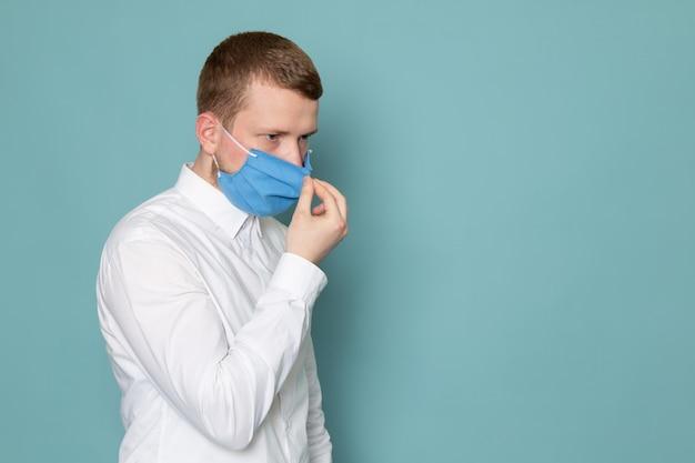 Een vooraanzicht jonge man in wit overhemd en een blauw masker op de blauwe ruimte