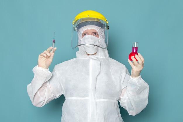 Een vooraanzicht jonge man in wit speciaal pak en gele speciale helm houden oplossing op de blauwe muur man pak gevaar speciale uitrusting kleur