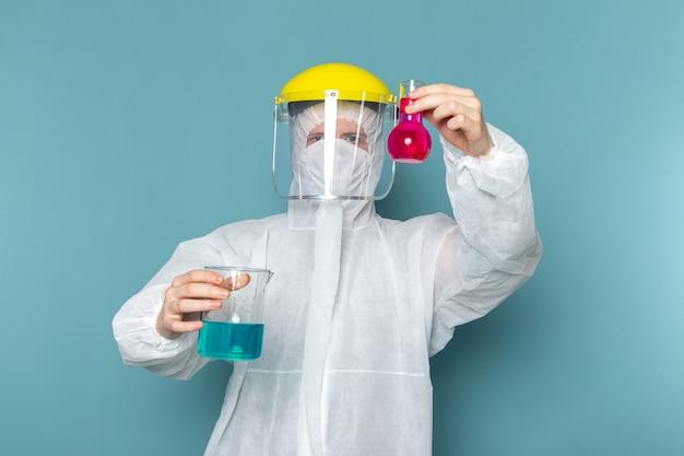 Een vooraanzicht jonge man in wit speciaal pak en gele speciale helm houden oplossingen op de blauwe muur man pak gevaar speciale uitrusting kleur