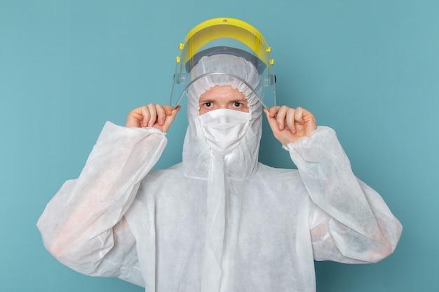 Een vooraanzicht jonge man in wit speciaal pak en gele speciale helm op de blauwe muur man pak gevaar speciale uitrusting kleur