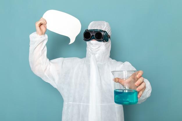 Een vooraanzicht jonge man in wit speciaal pak en met wit bord en oplossing op de blauwe muur man pak gevaar speciale uitrusting kleur