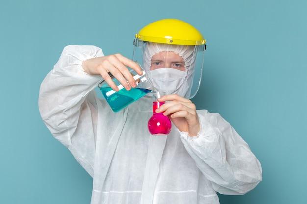 Een vooraanzicht jonge man in wit speciaal pak mengen oplossingen op de blauwe muur man pak gevaar speciale apparatuur kleur