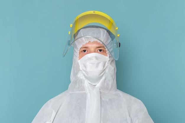 Een vooraanzicht jonge man in wit speciaal pak met speciaal hoofdmasker op de blauwe muur man pak gevaar speciale uitrusting kleur