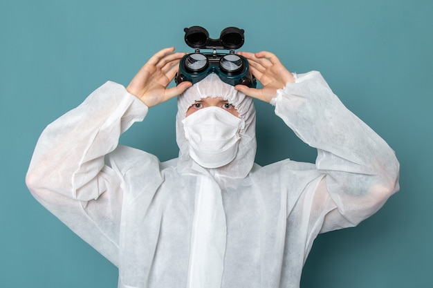 Een vooraanzicht jonge man in wit speciaal pak speciale zonnebril opstijgen op de blauwe muur man pak gevaar speciale uitrusting kleur