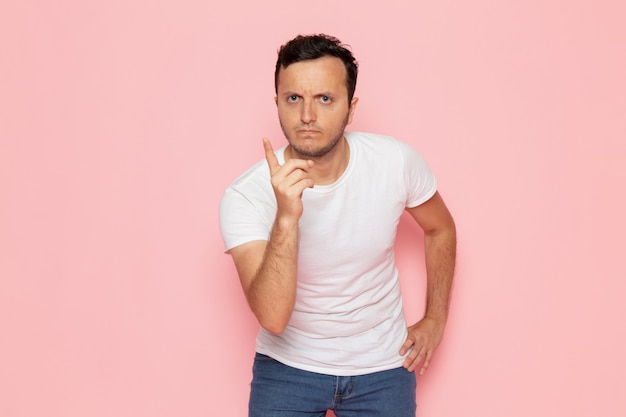 Een vooraanzicht jonge man in wit t-shirt en spijkerbroek bedreigend op het roze bureau man kleur emotie pose