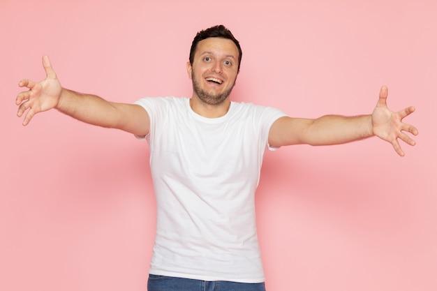 Een vooraanzicht jonge man in wit t-shirt en spijkerbroek met opgetogen uitdrukking op het roze bureau man kleur emotie pose